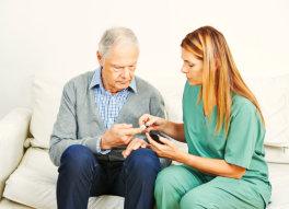 caregiver helping senior man with his medication