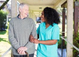 caregiver walking with senior man