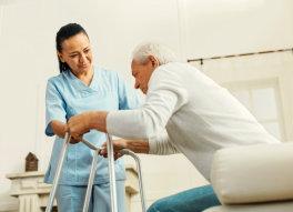 caregiver helping senior man stand-up
