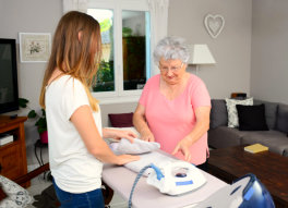 caregiver and senior woman doing some household chores