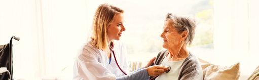 nurse with stethoscope checking senior woman