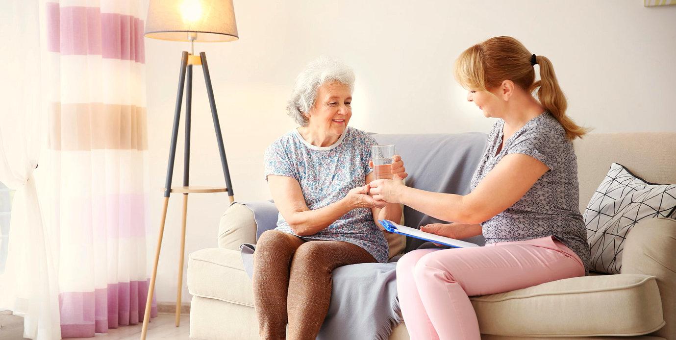 caregiver giving medication to a senior woman