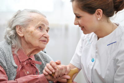 caregiver holding hands with senior woman