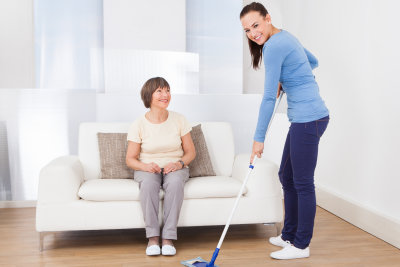 caregiver cleaning floor with mop while senior woman watching her