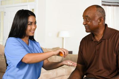 caregiver giving senior man his medication