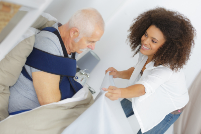 caregiver helping senior man with his beddings